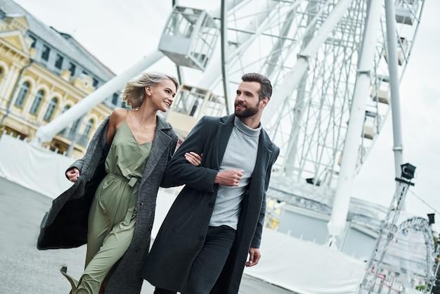 Romantyczna randka na świeżym powietrzu młoda para spacerująca po parku rozrywki, trzymająca się za ręce uśmiechnięta zrelaksowana