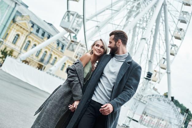 Romantyczna randka na zewnątrz młoda para spacerująca po parku rozrywki, trzymająca się za ręce, rozmawiająca z uśmiechem