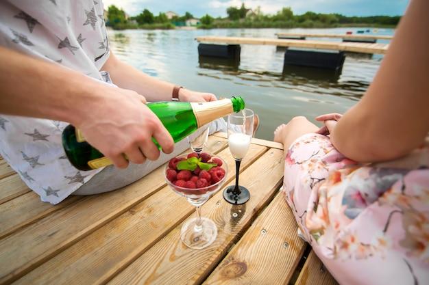 Romantyczna randka niespodzianka. młody chłopak i dziewczyna na drewnianym molo. facet nalewa szampana do kieliszków.
