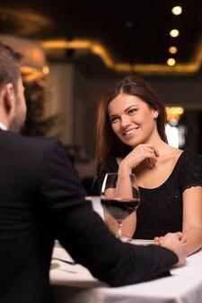 Romantyczna randka w restauracji. piękna młoda para rozmawia ze sobą i uśmiecha się podczas spędzania czasu w restauracji?