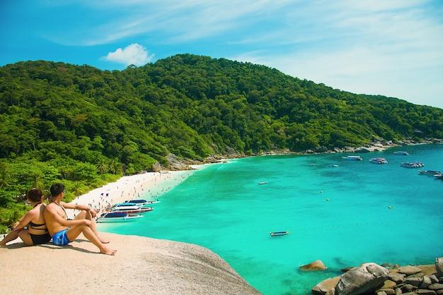 Romantyczna scena młodej miłości pary obsiadanie z relaksować i szczęściem na plaży w similan wyspach