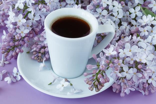 Romantyczna ściana z filiżanką herbaty, kwiatami bzu