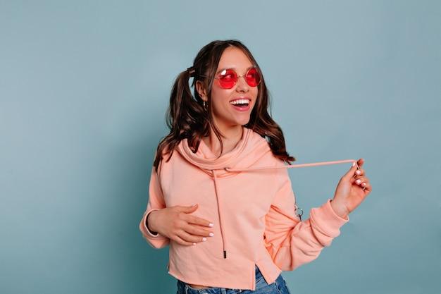 Romantyczna śliczna dziewczyna w okrągłych różowych okularach i różowym swetrze pozuje z uśmiechem i odwraca wzrok na odizolowanej niebieskiej ścianie