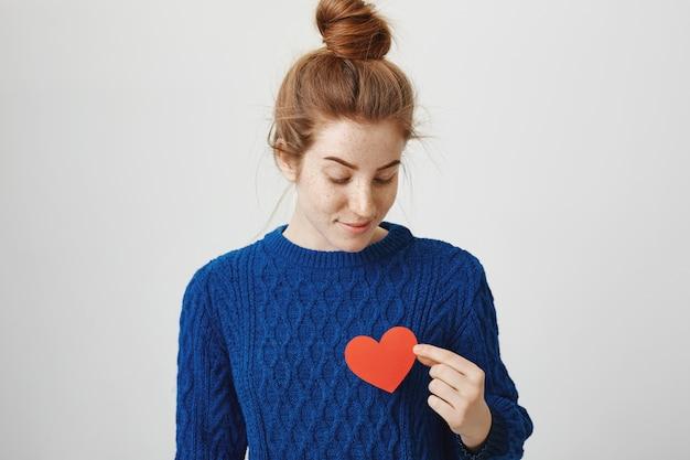 Romantyczna śliczna ruda dziewczyna trzyma znak serca