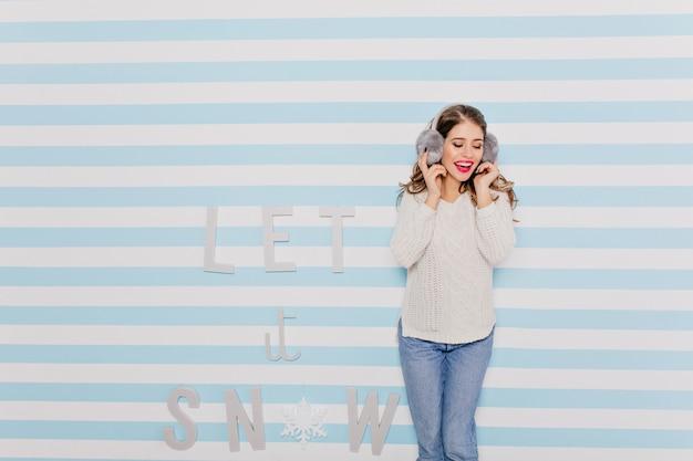 Romantyczna, słodka pani w modnym zimowym stroju słuchająca muzyki w śmiesznych dużych słuchawkach. portret długowłosej dziewczyny o jasnym wyglądzie
