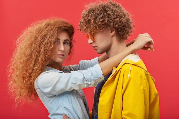 Romantyczna słodka piękna para z rudymi włosami kręconymi w stylowe ubrania przytulanie