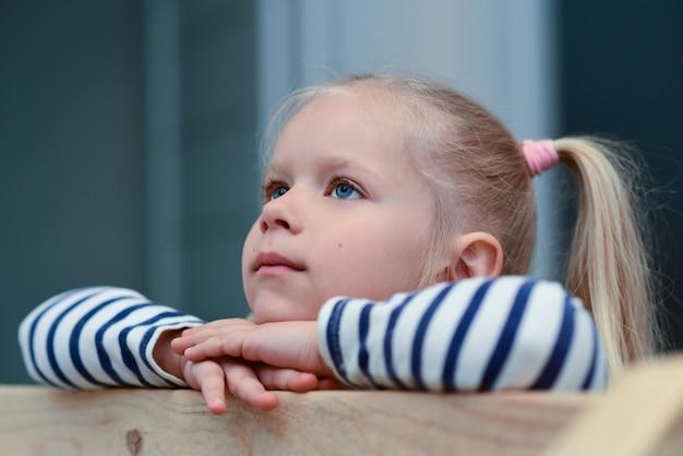 Romantyczna smutna dziewczyna na drewnianej poręczy spogląda i jest smutna
