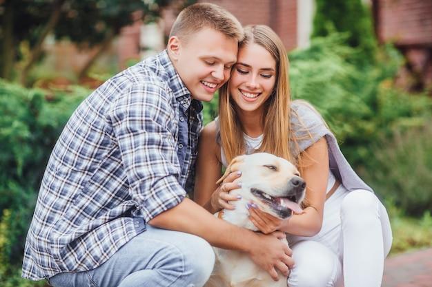 Romantyczna szczęśliwa rodzina w miłości spędza czas z labradorem w naturze. szczęśliwa para pieści swojego żółtego labradora.