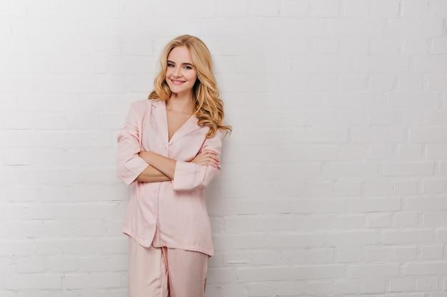Romantyczna uśmiechnięta dziewczyna stojąca w pobliżu białej ściany w godzinach porannych. szczęśliwa kobieta kręcone w różowym garniturze z założonymi rękami.