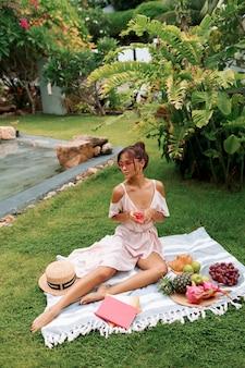 Romantyczna wdzięczna modelka azjatycka siedzi na kocu, pije wino i cieszy się letnim piknikiem w tropikalnym ogrodzie.