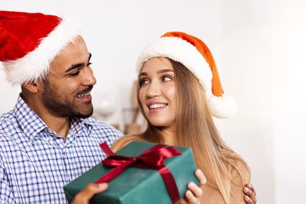 Romantyczna, wieloetniczna para w świątecznych czapkach wymieniająca prezenty