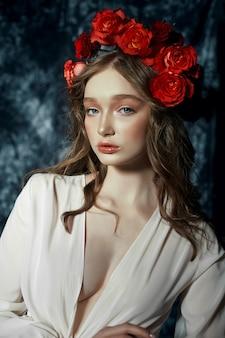 Romantyczna wiosna portret młodej kobiety blondynka z wieńcem z czerwonych kwiatów róży