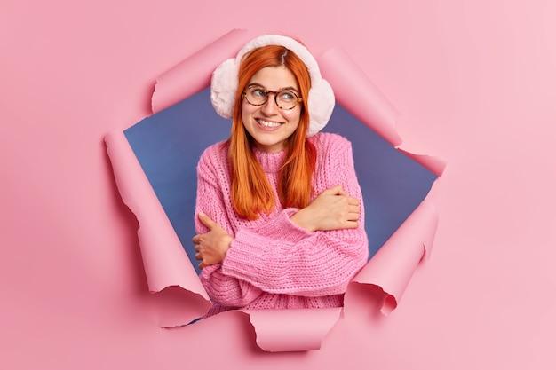 Romantyczna, zadowolona rudowłosa kobieta obejmuje się i uśmiecha się delikatnie, ciesząc się noszeniem ciepłych i wygodnych nauszników swetra, gdzieś radośnie wygląda.