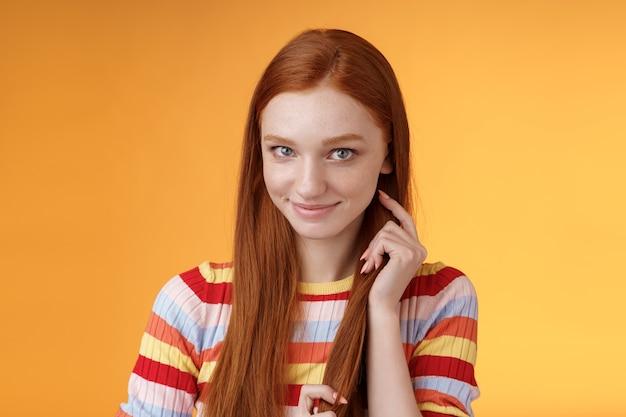 Romantyczna zalotna, nieśmiała, atrakcyjna ruda dziewczyna 20-latka dotykająca kosmyków włosów uśmiechnięta głupawo skromna zerkająca na aparat zalotna robiąca urocze spojrzenia chcę uwieść faceta wyrażającego współczucie, pomarańczowe tło
