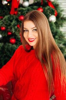 Romantyczna zimowa hipster dziewczyna w dzianym czerwonym swetrze w pobliżu choinki