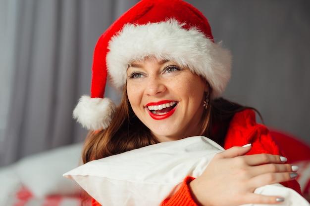 Romantyczna zimowa hipsterska dziewczyna w dzianinowym swetrze i świątecznym kapeluszu leżąca na łóżku