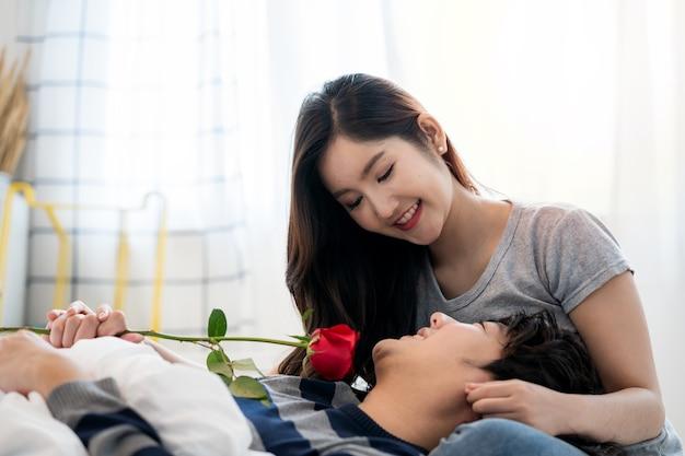 Romantyczne azjatyckie pary w sypialni młody mężczyzna dający czerwoną różę ładnej kobiecie