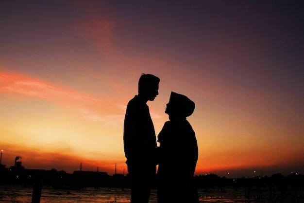 Romantyczne chwile dwóch par pod niebem o zachodzie słońca