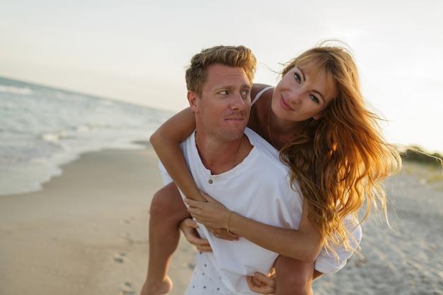 Romantyczne chwile szczęśliwej pary europejskiej zakochanej rozkoszującej się tropikalnymi wakacjami na plaży.