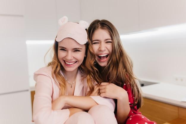 Romantyczne dziewczyny z lśniącymi włosami, śmiejąc się, siedząc w kuchni. cudowne kaukaskie siostry w piżamie pozują z przyjemnością w jasnym pokoju.