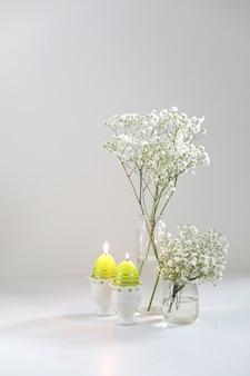 Romantyczne eleganckie bukiety z gipsophyla białych kwiatów i świec na białym tle. skopiuj miejsce. koncepcja wielkanocna.