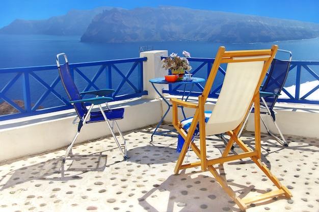 Romantyczne greckie wakacje na najpiękniejszej wyspie santorini. stolik kawowy z widokiem na kalderę i wulkan. grecja