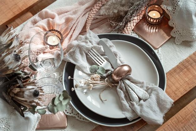 Romantyczne nakrycie stołu z płonącymi świecami i suszonymi kwiatami na wesele z wieloma dekoracyjnymi detalami