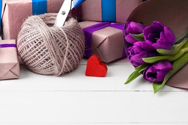 Romantyczne pudełka z kwiatami na białej drewnianej ścianie