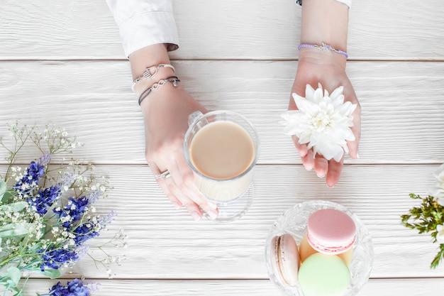 Romantyczne śniadanie kobieta, leżak na płasko. piękne kobiece ręce trzymając filiżankę kawy latte i biały kwiat, danie z makaronikiem i kwiatami na białym drewnianym stole, widok z góry