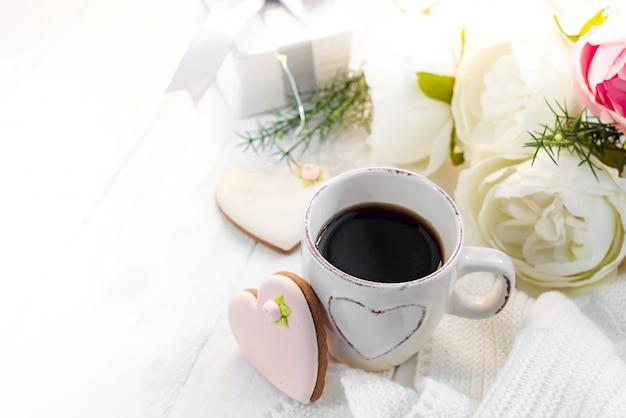 Romantyczne śniadanie w łóżku. kawa, ciasteczka, pudełko i kwiat na drewnianym stole. walentynki koncepcja