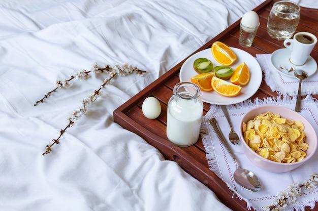 Romantyczne śniadanie w łóżku z wiosennymi kwiatami. światło okna, kopia przestrzeń