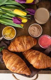 Romantyczne śniadanie z chrupiącymi rogalikami, kremem czekoladowym z dżemem, kawą i kolorowymi tulipanami