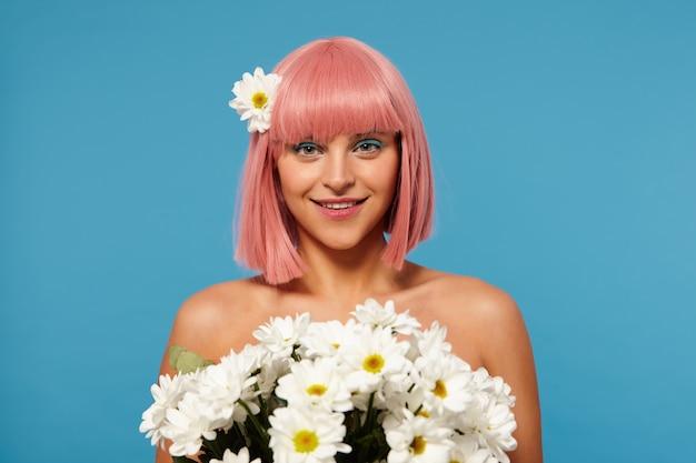 Romantyczne zdjęcie młodej uroczej różowowłosej kobiety z kolorowym makijażem, trzymającej ogromny bukiet kwiatów i wyglądającej pozytywnie z czarującym uśmiechem, odizolowane
