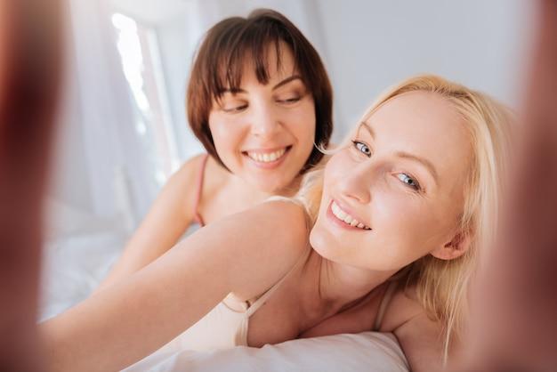 Romantyczne zdjęcie. piękne, zachwycony blondynka trzyma aparat i uśmiecha się, patrząc w to