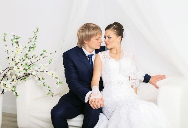 Romantyczni nowożeńcy pozowanie na luksusowej białej kanapie