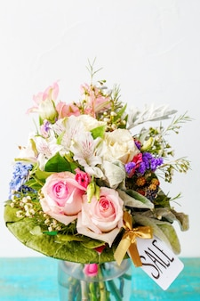 Romantyczny bukiet różowych róż, lilii, zielonych liści na drewnianym niebieskim stole