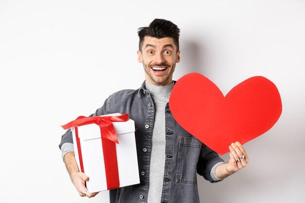 Romantyczny chłopak przyniesie prezent i walentynkową kartkę na randkę, uśmiechając się radośnie do kamery, świętując biały dzień z kochankiem, studio.