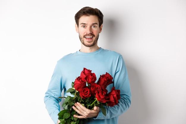 Romantyczny chłopak przynosi piękny bukiet czerwonych róż na walentynki, spotyka się z dziewczyną, mówi kocham cię, stoi namiętnie na białym tle