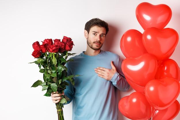 Romantyczny facet wyrazić swoją miłość w walentynki prezentami, przynieść bukiet czerwonych róż i balonów, trzymając rękę na sercu, stojąc na białym