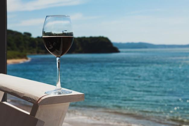 Romantyczny kieliszek wina na balustradzie, siedząc na plaży na wybrzeżu, wino na tle nieba z chmurami.