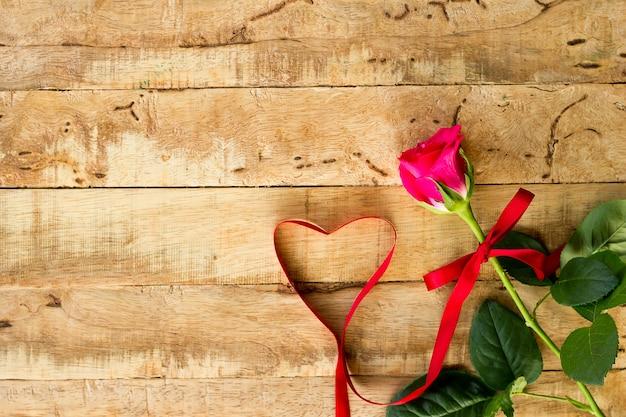 Romantyczny kwiecisty ramowy tło / walentynka dnia tło / różowe róże na drewnianym tle