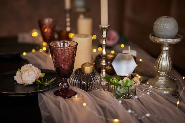 Romantyczny lub weselny zestaw obiadowy lub świąteczny stół, brązowa, różowa i złota dekoracja ze świecami i girlandą. zbliżenie szczegółów, selektywna ostrość