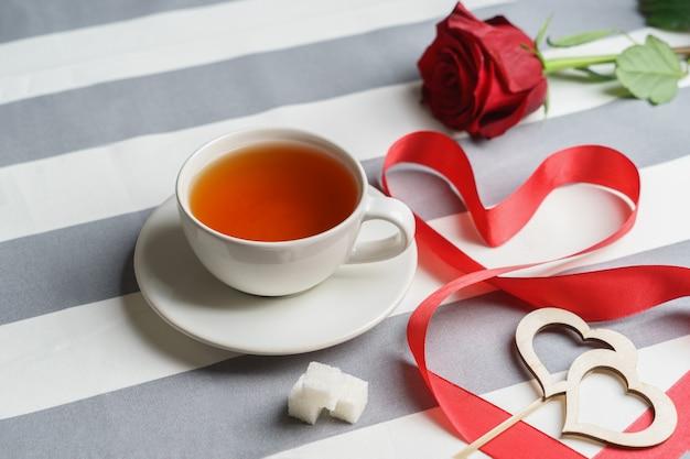 Romantyczny martwa natura z filiżanką herbaty i jasnymi czerwonymi atrybutami wakacyjnymi.