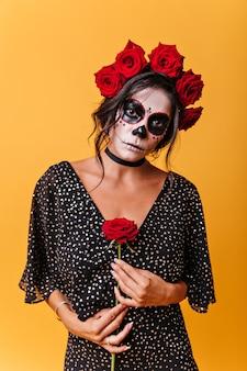Romantyczny meksykański delikatnie trzyma różę. portret tajemniczej kobiety z kwiatami we włosach i makijażem halloween.