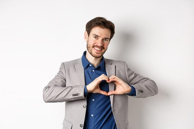 Romantyczny mężczyzna w garniturze pokazuje znak serca i uśmiecha się, kocha swoją dziewczynę, stojąc na białym tle, spowiadając się kochankowi.
