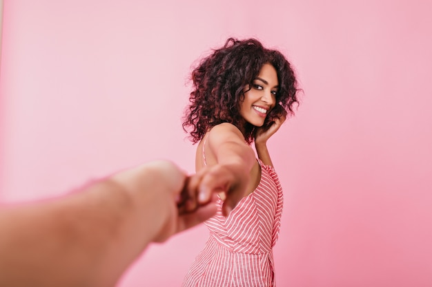 Romantyczny, młody amerykanin z kręconymi włosami romantyczny pozuje, trzymając mężczyznę za rękę. letnia różowa górna brunetka uśmiecha się czule.