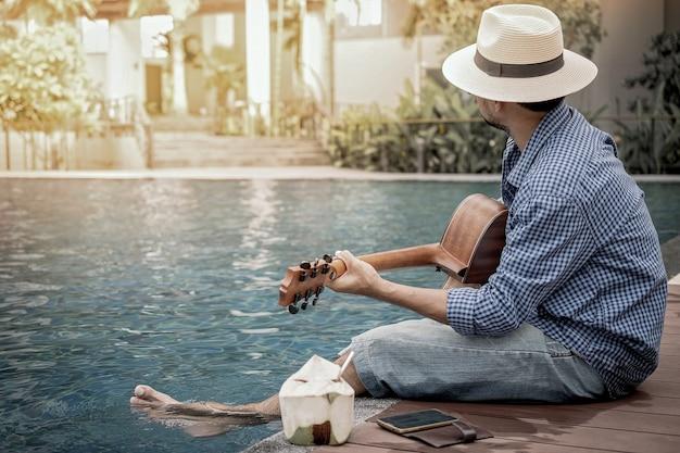 Romantyczny młody człowiek siedzi na basenie o zachodzie słońca z grą na gitarze