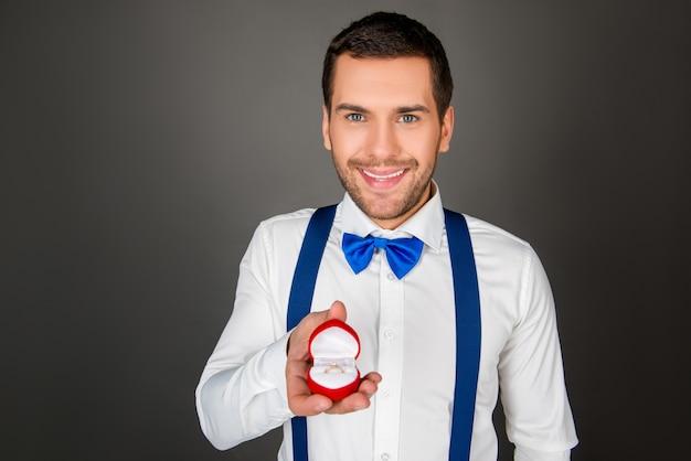 Romantyczny młody człowiek z pierścionkiem zaręczynowym