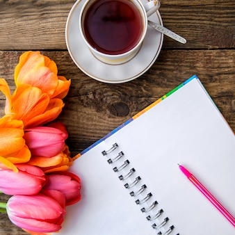 Romantyczny obrazek z tulipanami, herbatą, notatnikiem na drewnianym tle