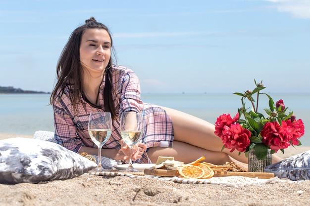 Romantyczny piknik na piaszczystym brzegu plaży z kwiatami i kieliszkami drinków. pojęcie wakacji.